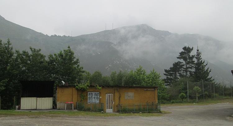 A misty hilly backdrop to a ramshackle hut by the side of the N634 in Northern Spain