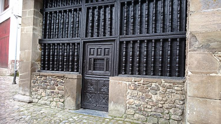 A wooden carved and turned doorway and door all painted black at Potes
