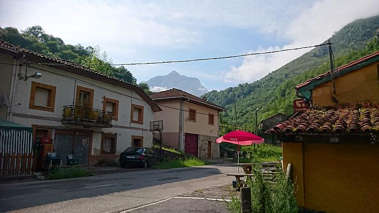 Old Spanish houses against towering mountains heading towards The Picos