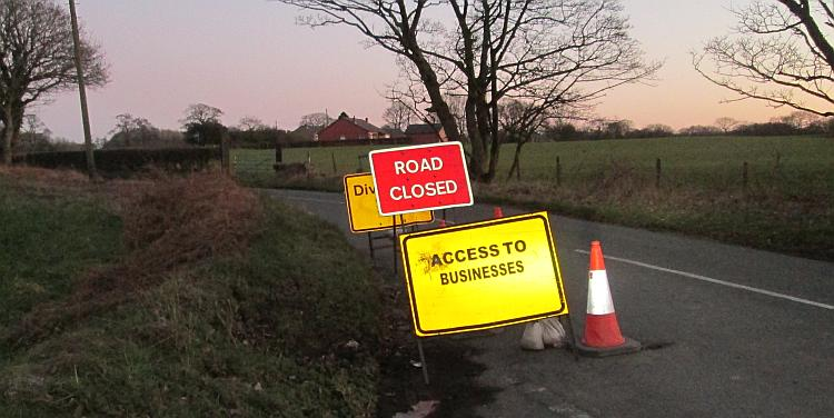 3 signs showing road closed, diversion and access to businesses only