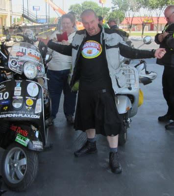 Stephen is posing in his black kilt next to the Vespa