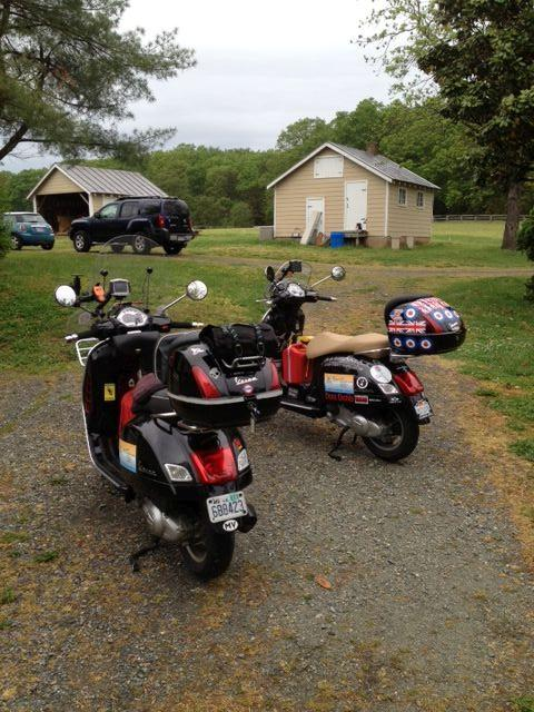 2 scooters with luggage and stickers at a Virginian farm