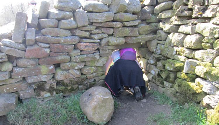Sharon is crawling though a small hole in a drystone wall