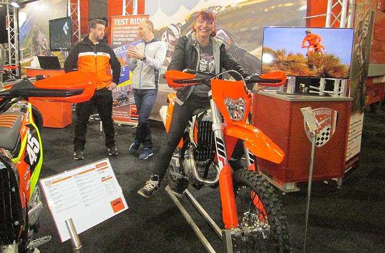 Sharon is sat on a very tall KTM off road bike at a bike show. Her feet are about 1 foot from the floor