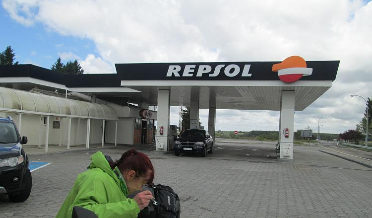 An ordinary Repsol garage in Spain and Sharon looking at something on her bike seat