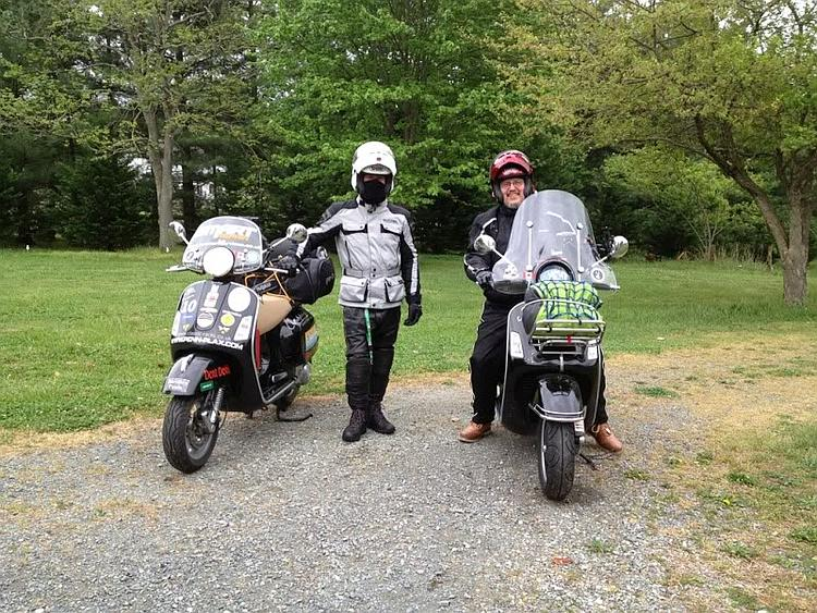 Stephen and Rick in their riding kit with their scooters ready to roll