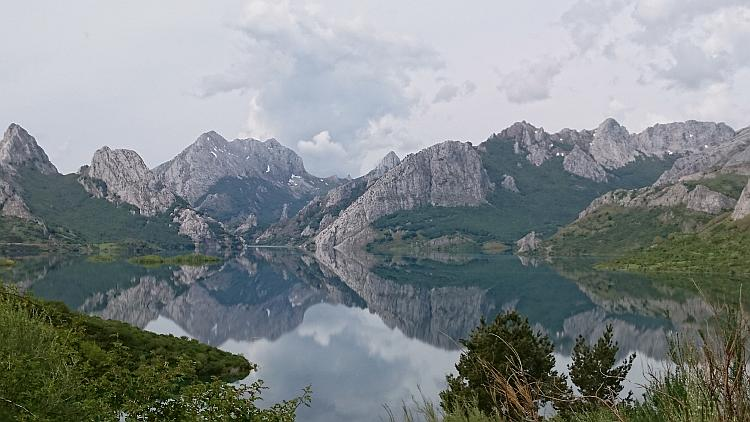 Sharp angular and snow tipped mountains reflected perfectly in the water of a lake in The Picos