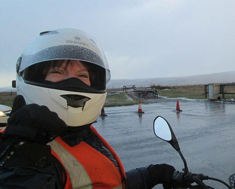 Sharon in her helmet and bike gear on a very very wet day giving a thumbs up and smiling