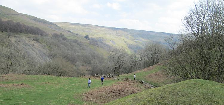 Several walkers make their way down a grassy path in the Dales