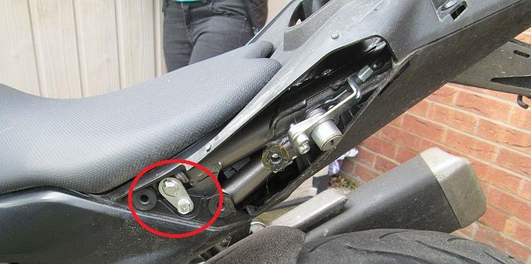 The rear subframe of the bike is now exposed and the seat fixing pins are circled