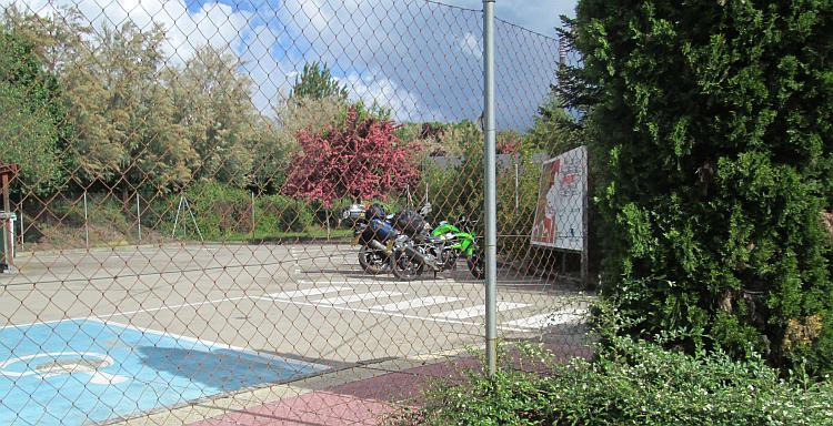 Behind a wire fence the bikes are in a car park surrounded by trees at the site