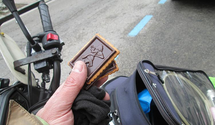 2 biscuits with simple icons in the chocolate covering are held in Ren's hands by the bike