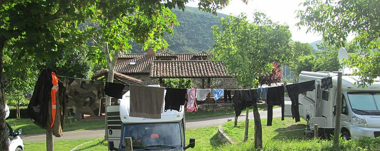 Clothes on a line amidst trees and campervans at the campsite in Potes