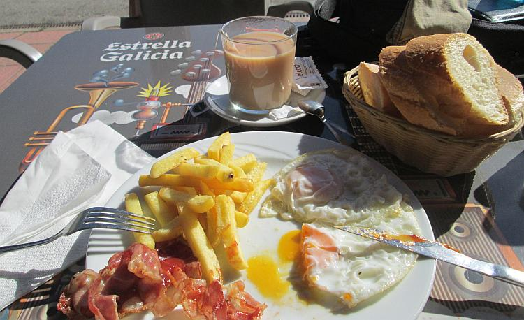A plate with bacon chips egg and a cup of tea looking very tasty at camping de la demanda