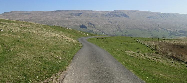 An empty tarmac lane winds across the hills of North Yorkshire