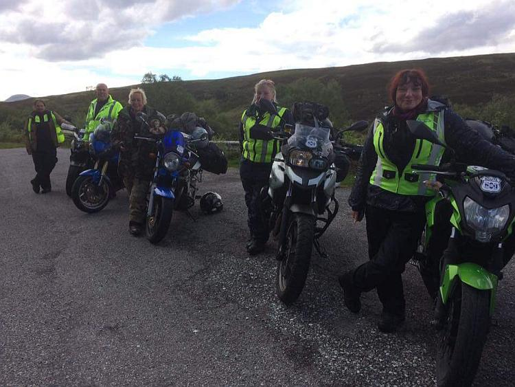 Sharon, Ren and some other biker all posing for the camera on a Highland road