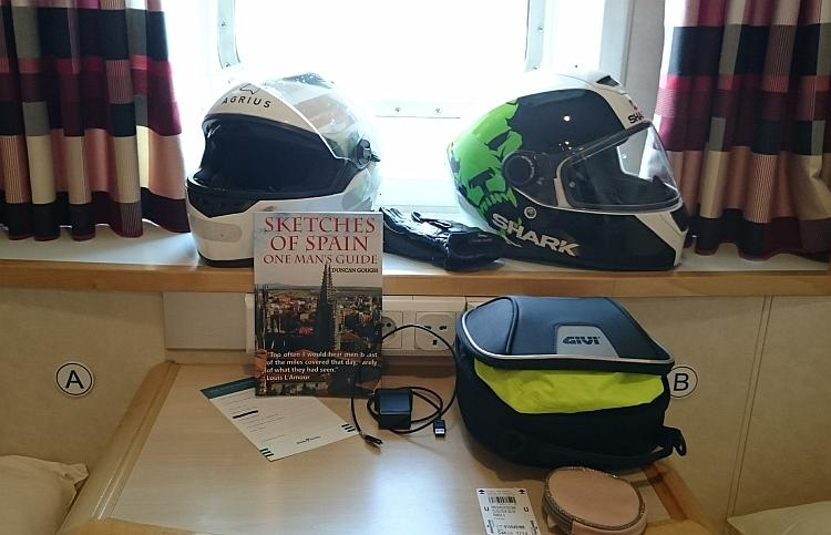 2 helmet in the window recess and a book on the small table between the beds of the Ferry cabin