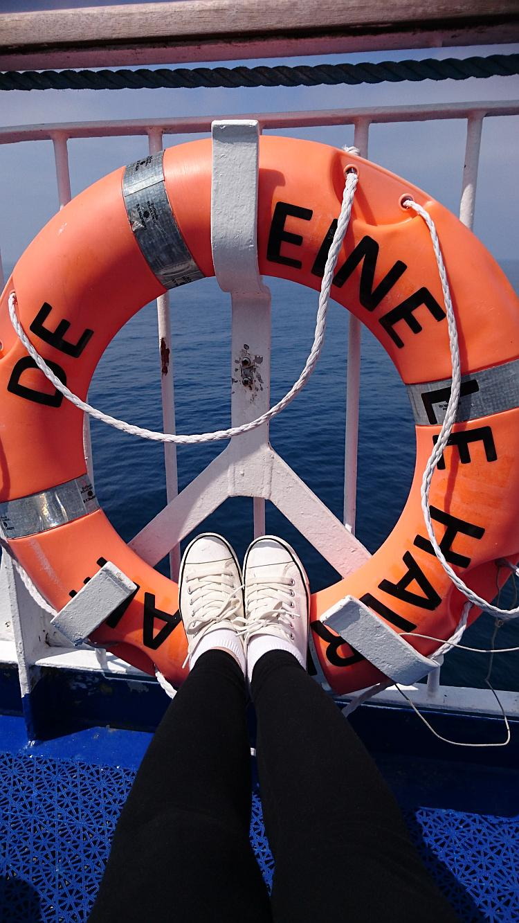 Sharon's feet are resting in the centre of a bright orange ring lifebelt on the ferry