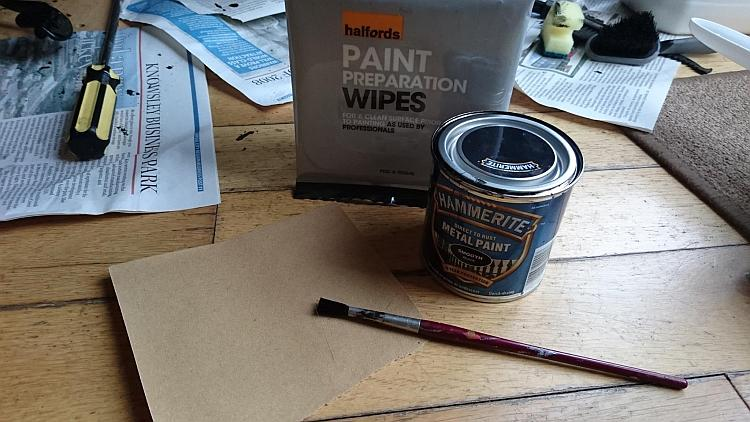 A tin of hammerite, some paint preparation wipes and a small paint brush on Sharon's floor