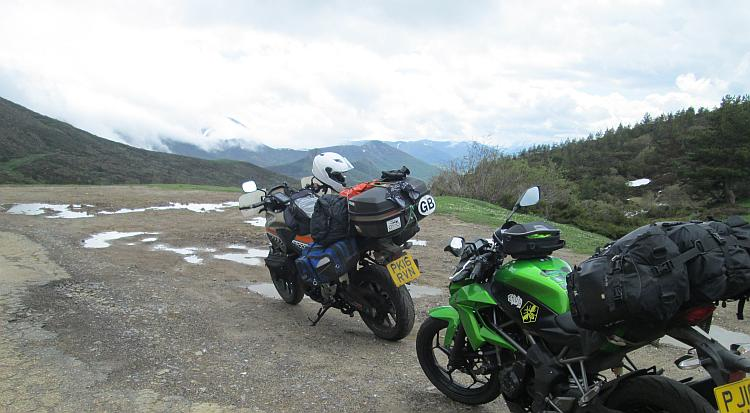 The 2 motorcycles with their camping kit on the peak of the pass, there's a little snow here and there