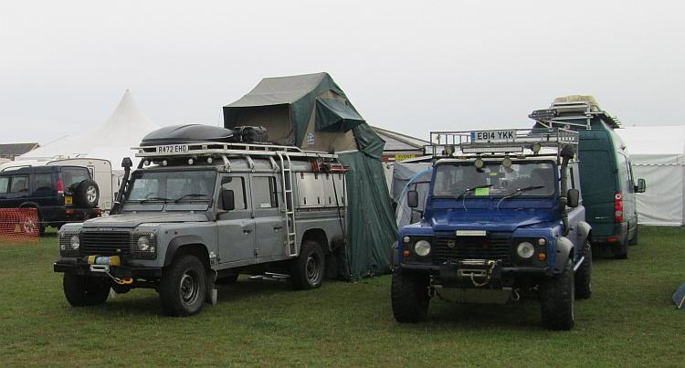 2 Land Rovers set up for overland travel with fold out tents on the roof.
