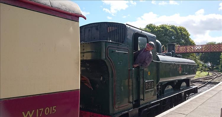 The driver of the steam engine leans out to ensure everyone is on the carriages