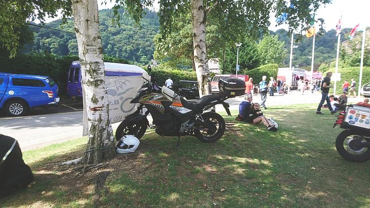Ren's CB500X between 2 trees and with the BAT banner at the Bike Fest