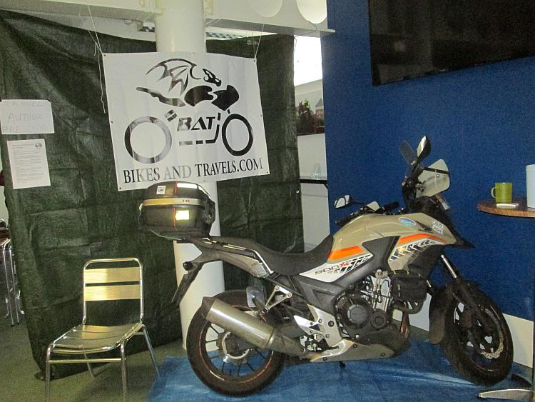 Ren's CB500X and a large bat logo on a banner at the Stratford show