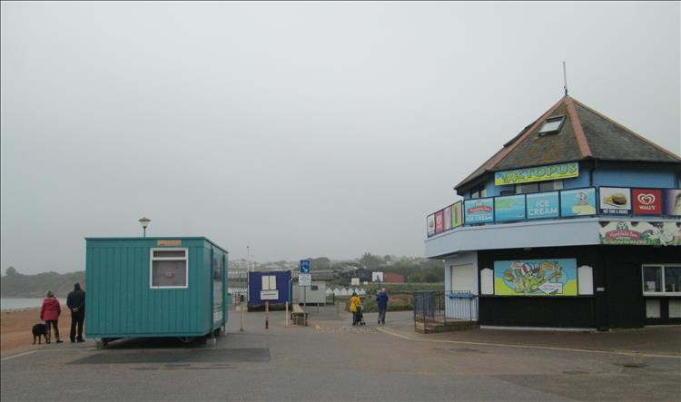 Closed shops, a container, grey skies and mist at Goodrington Sands