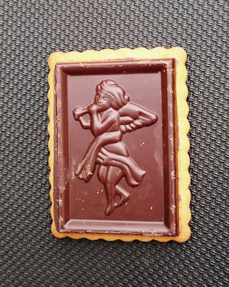 A chocolate covered biscuit with an angel playing a pipe moulded into the chocolate