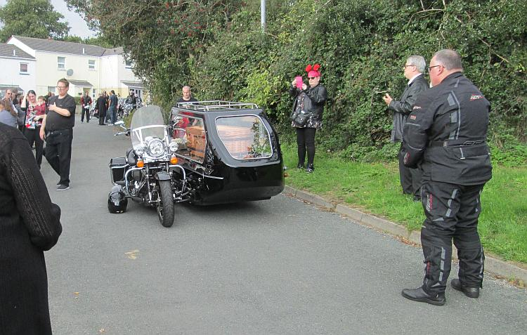 A motorcycle and sidecar, with the wicker coffin in the sidecar
