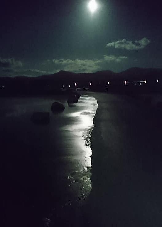 The bright moon illuminates water lapping over the road as the tide comes in