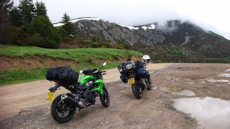 The 2 bikes loaded with camping gear on top of a mountain with some snow in the background
