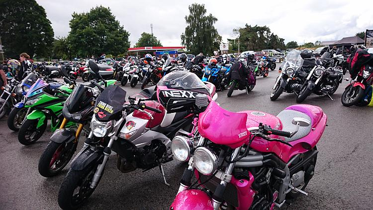 A range of motorcycles fill the car park in the rain at the Truck Stop