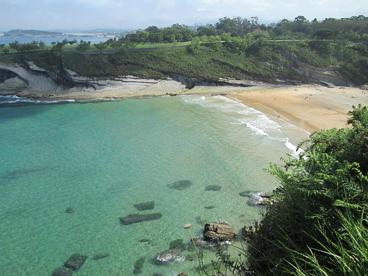 Turquoise waters and golden sands, steep cliffs and a small horseshoe bay in Santander