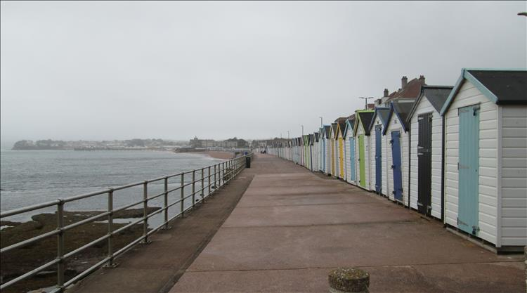 A long line of beach huts by the sea wall at Preston Sands Devon. The weather is still grey