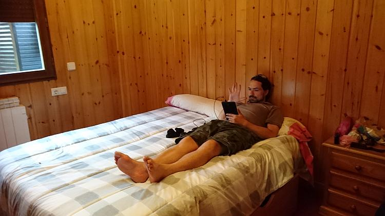 Ren relaxing on the double bed of the wooden lodge
