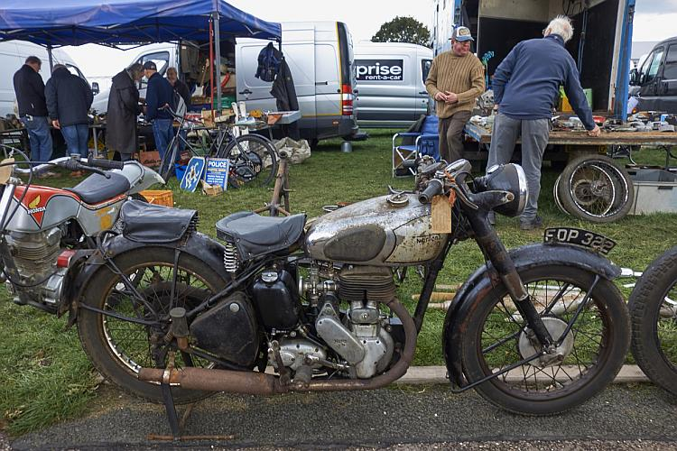 A rusty old Norton motorcycle with a price tag on it for sale outside the show