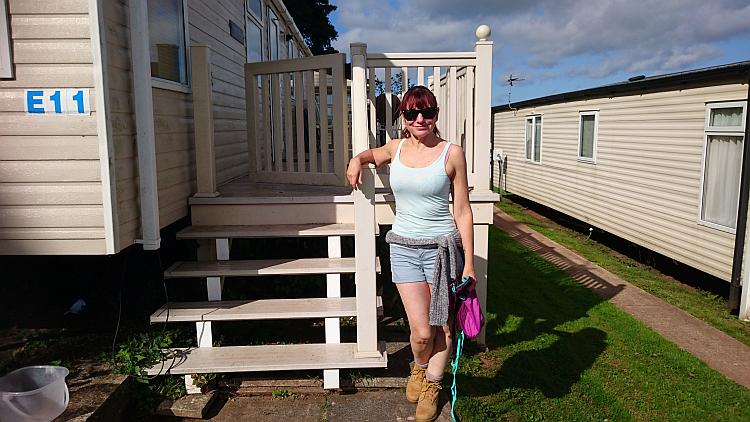 Sharon in shorts and vest and shade in the sunshine at the caravan near Brixham
