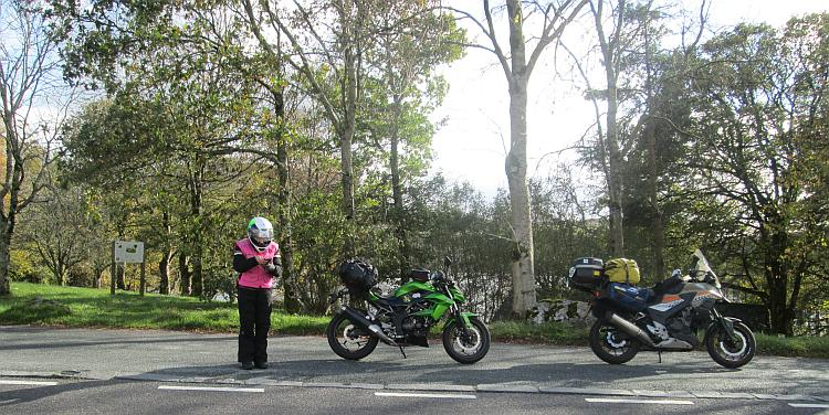 Sharon is looking at her phone next to the motorcycles amidst trees and gorgeous sunshine