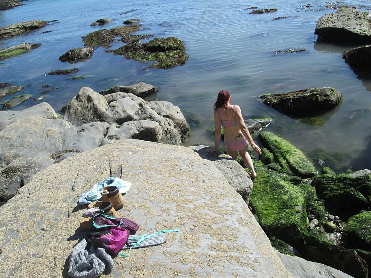 Sharon in her underwear is climbing down the coastal rocks into the sea at Devon