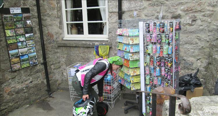 Sharon picking up her bike gear amidst postcards and keyrings outside a local shop