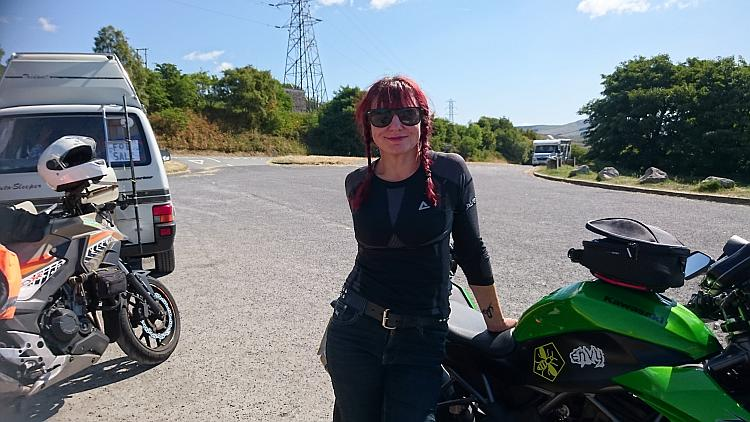 Sharon is looking cool in shades and bike gear by the motorcycles and in the sun