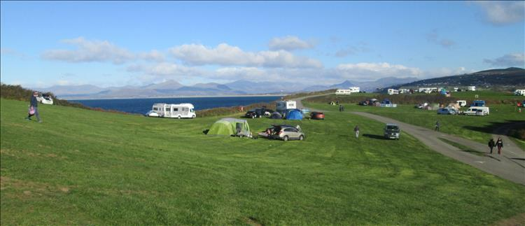 A rolling field with a sprinking of campers, behind the bay and the welsh mountains in the autumnal sun