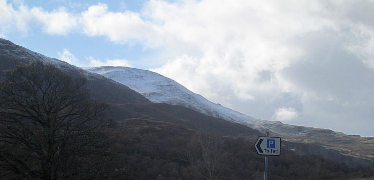 One rounded mountain in North Wales has a good layer of snow under light cloud and blue skies