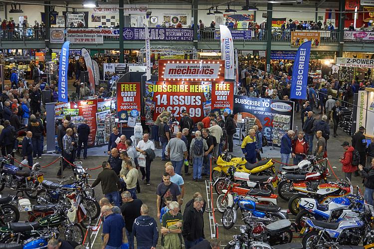 Looking down from a balcony we see a plethora of stall and banners all motorcycle related