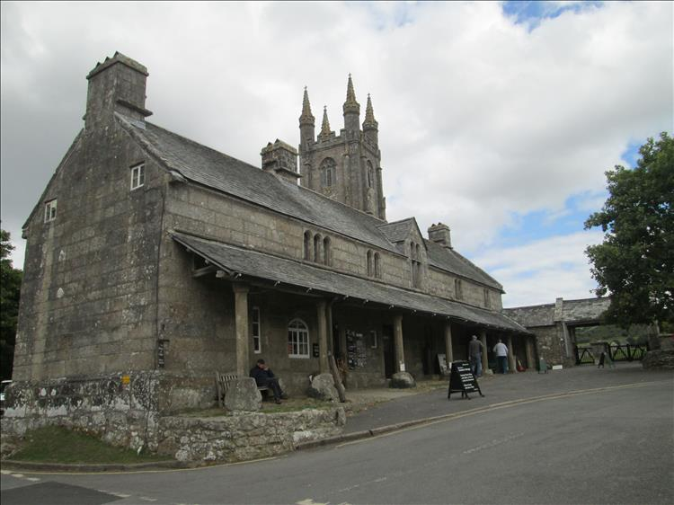 A large stone building with a information centre and Widecome in the Moor church behind it