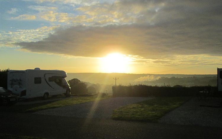 Hazy clouds and light blue skies and the sun look huge as it rises above the Horizon in Cornwall