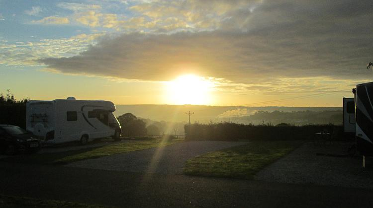 The sun is rising into a blue sky with light clouds over a campsite in Cornwall