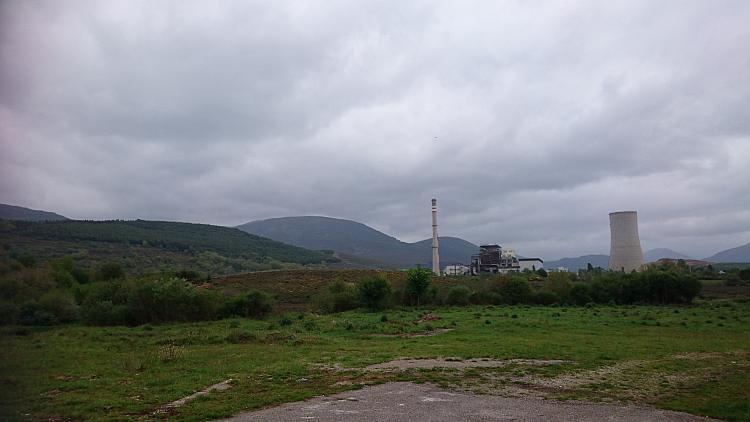 Big hills and green surrounding, among it all are the towers and massive building of a power station